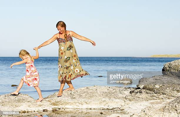 Mother with daughter walking on rocky coast