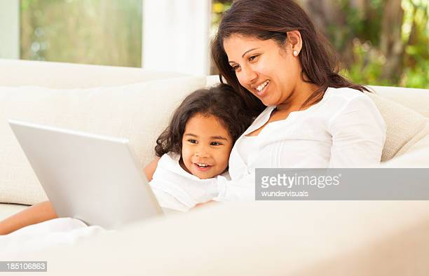 Mother With Daughter Working On Laptop