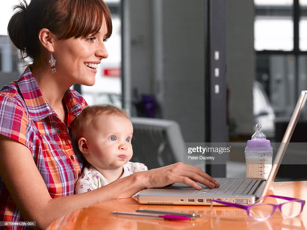 Mother with daughter (6-11 months) working on laptop : Stock Photo