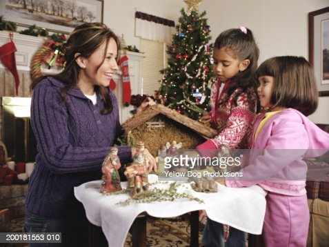 Mother with daughter's (3-7) fixing porcelain figurines and barn