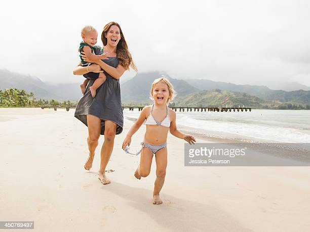 Mother with daughters (6-11 months, 2-3) on beach
