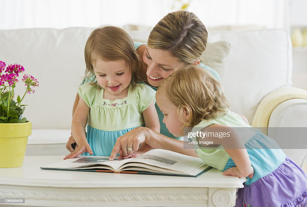 Mother with daughters (2-3) reading book in living room : Stock Photo