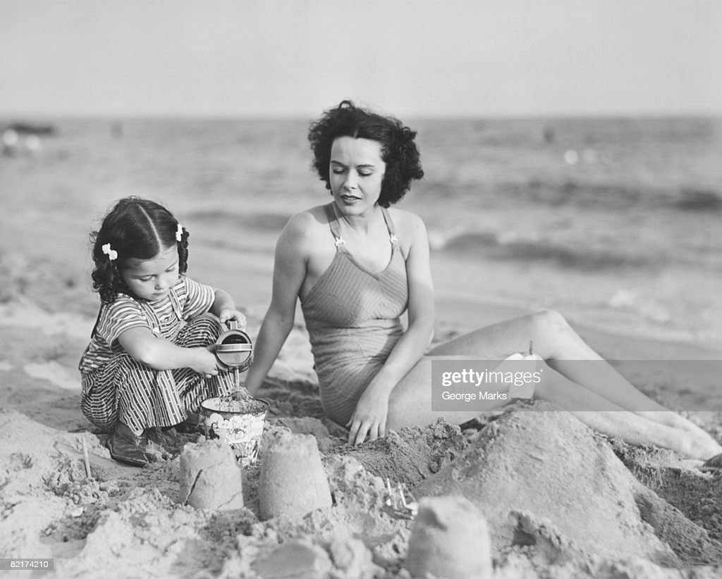 Mother with girl (2-3) playing in sand on beach, (B&W) : Stock Photo