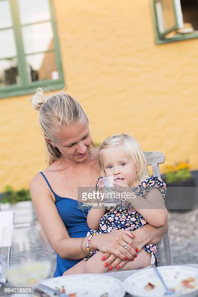 Mother with girl sitting at table