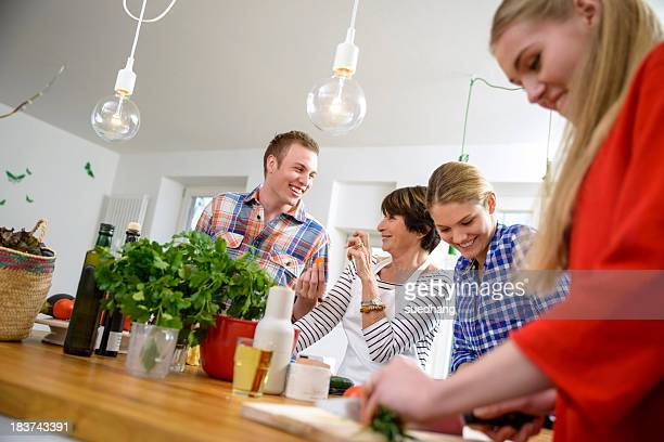 Mother with grown up children preparing food in kitchen