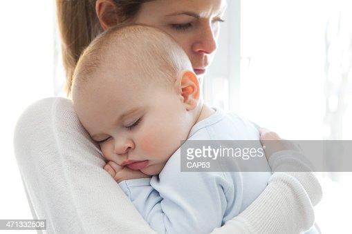 Madre con su bebé niño durmiendo en sus brazos
