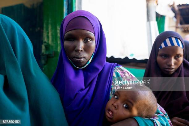 A mother with her child waits in line at World Food Program Supplemental Nutrition center in Dinsoor Somalia Somalia is in the grip of an intense...