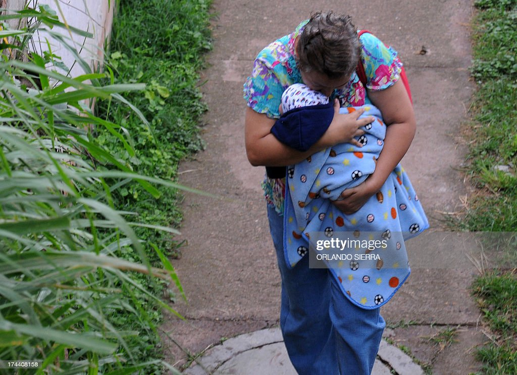 A mother with her child, who have symptoms of dengue fever, arrive at a hospital in Tegucigalpa on July 25, 2013. Authorities have issued dengue alerts in four nations across Central America, where alarm is rising as the mosquito-borne disease has infected 40,000 people and killed 16 this year alone. AFP PHOTO /Orlando SIERRA