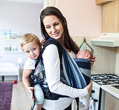 Beautiful young mother with her newborn son in sling and her daughter in baby carrier at home
