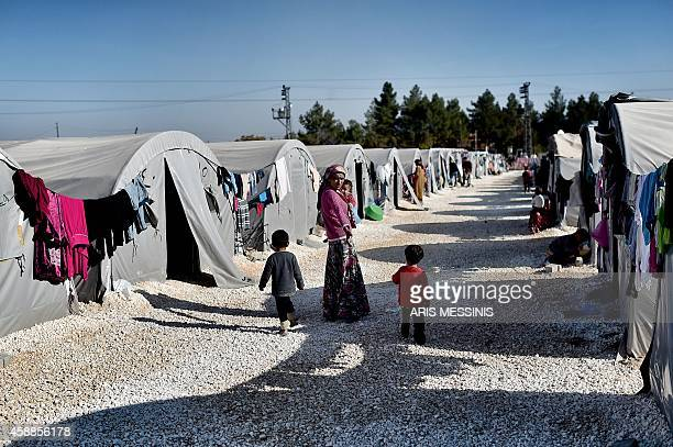 A mother with her children walks at a refugee camp in the town of Suruc Sanliurfa province on November 12 2014 AFP PHOTO / ARIS MESSINIS