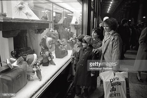 A mother with her children watching in amazement a shop window decked out for Christmas Milan 1981