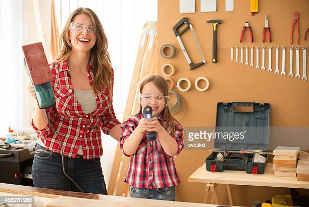 Mother with her cute little daughter in woodshop.