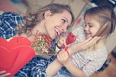 Daughter giving a bouquet of flowers to her mother.