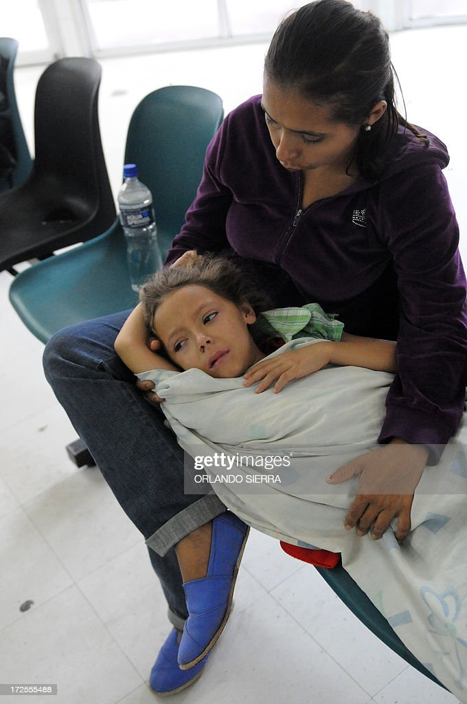 A mother with her daughter with symptoms of dengue fever await to be seen at Hospital Materno Infantil medical centre in Tegucigalpa on July 3, 2013. The disease vectored by the Aedes aegypti mosquito has killed ten people in Honduras so far this year. AFP PHOTO /Orlando SIERRA.