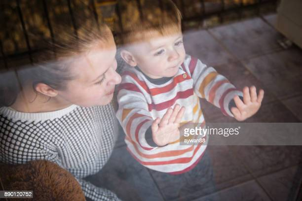 Mother with her little son looking out of window