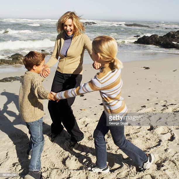 mother with her son and daughter playing ring-around-a-rosy on the beach