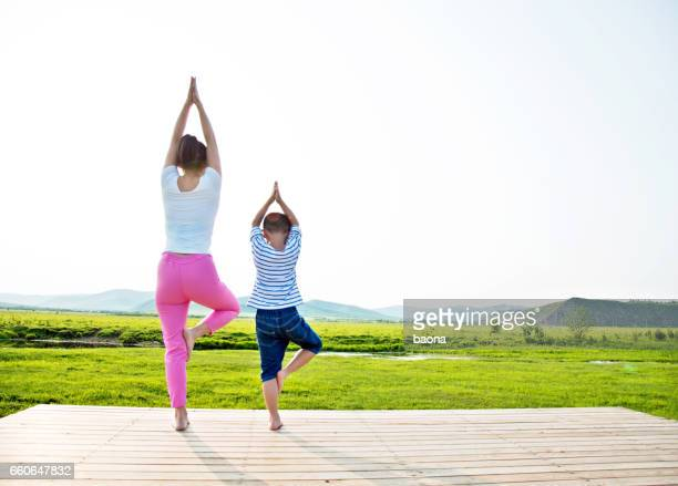 Mother with her son doing yoga in the nature
