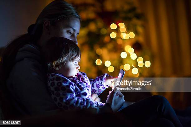 Mother with her son using a smartphone in the dark
