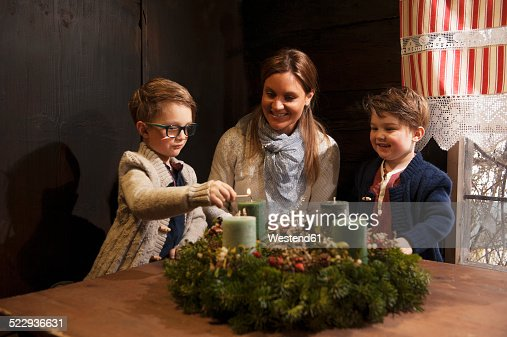 Mother with her two little sons lightning candles on a Advent wreath