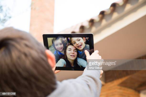 Mother with kids taking selfie photo with IPad tablet in funny moment and sunset light