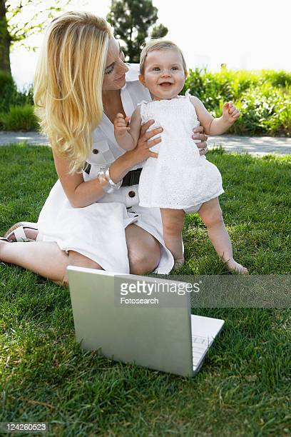 Mother with laptop computer holding baby girl