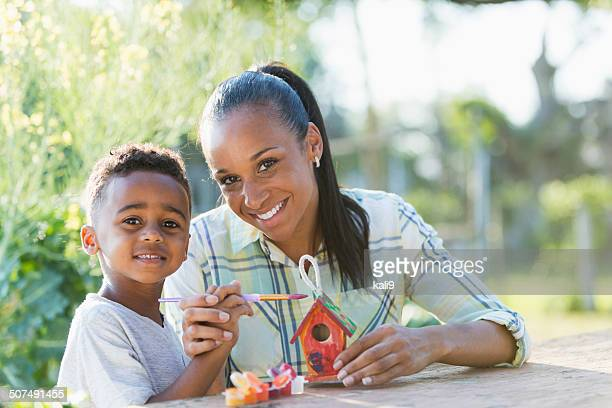 Mother with little boy painting bird house