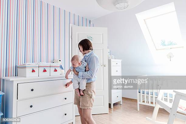 Mother with little child on hands, baby's room, white furnitures