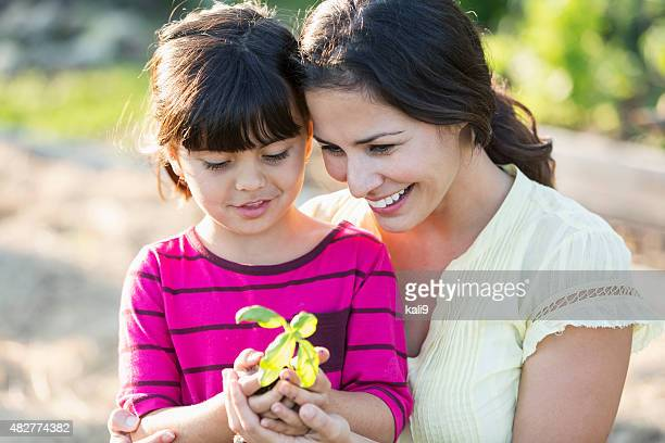 Mother with little girl holding seedling