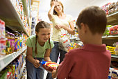 Mother with mischievous children at grocery store