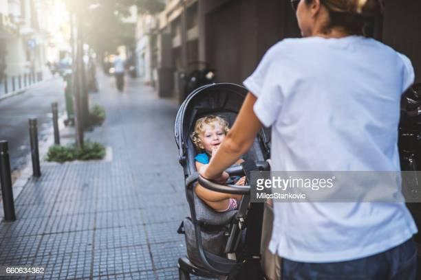 Mère avec pram en marche de la ville