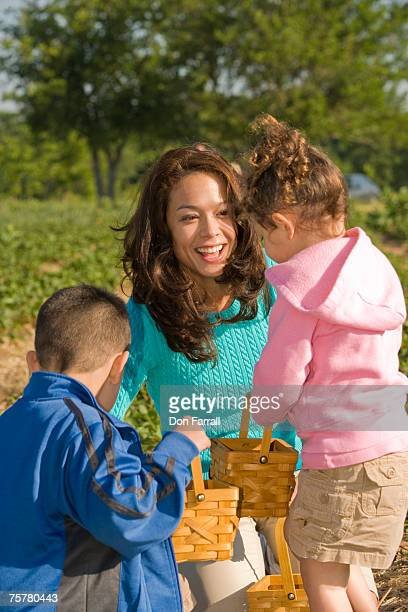 Mother with son (6-7) and daughter (3-4) in fields with baskets