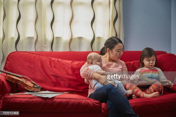 Mother with son and daughter on sofa reading book