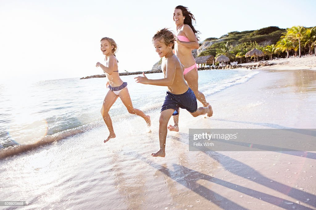 Mother with son (8-9) and daughter (10-11) running on beach : ストックフォト