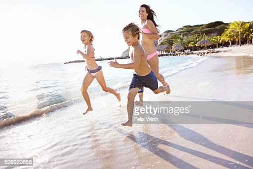 Mother with son (8-9) and daughter (10-11) running on beach : Stock Photo
