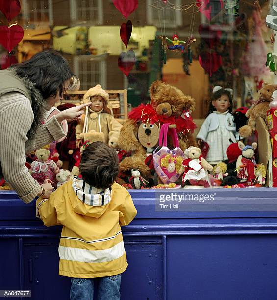Mother with son (4-6) looking in toy store window, rear view