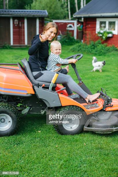 Mother with son on ride-on lawn mower