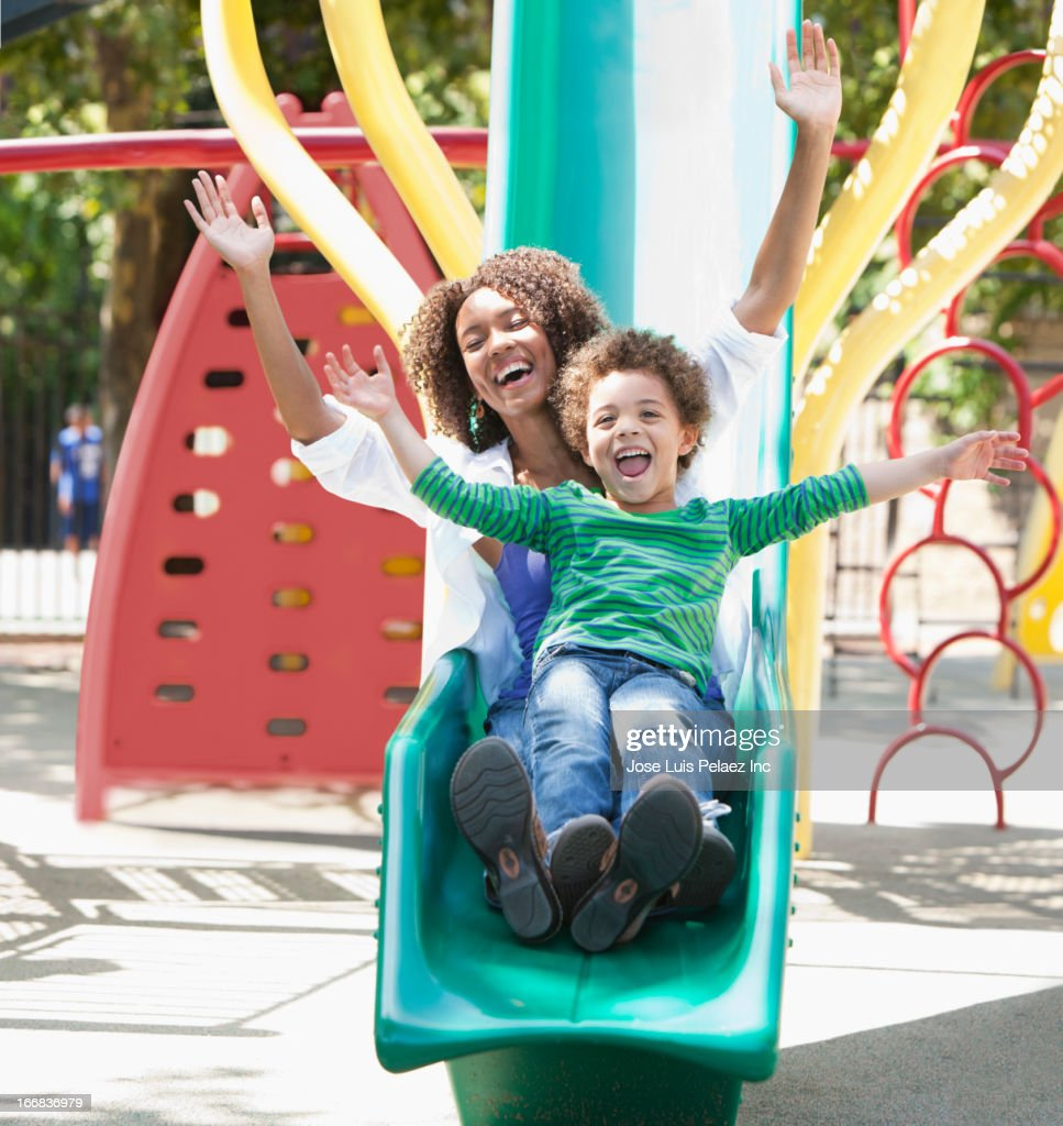 Mother with son on slide at playground