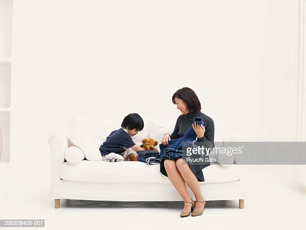 Mother with son (3-4) on sofa with puppy