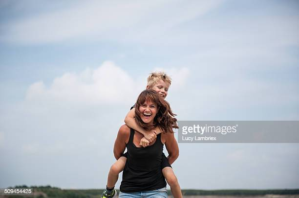 Mother with son piggyback riding, smiling