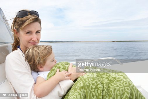 Mother with son (15-18 months) under blanket sitting on boat : Foto de stock
