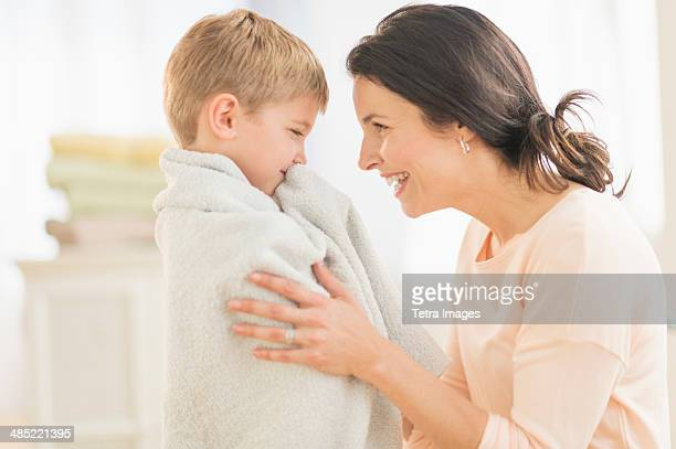 Mother with son (6-7) wrapped in towel