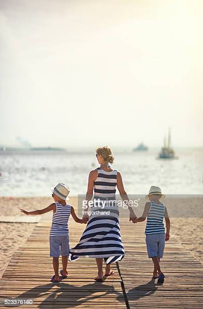 Mother with sons walking to the beach
