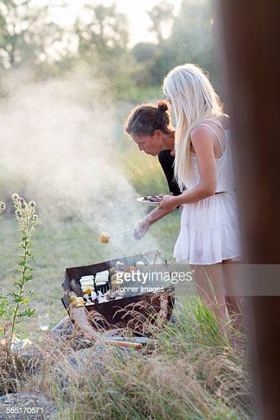 Mother with teenage daughter having barbecue