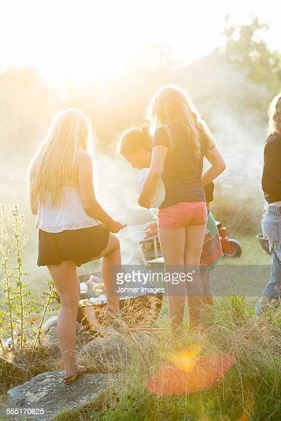 Mother with teenage daughters having barbecue