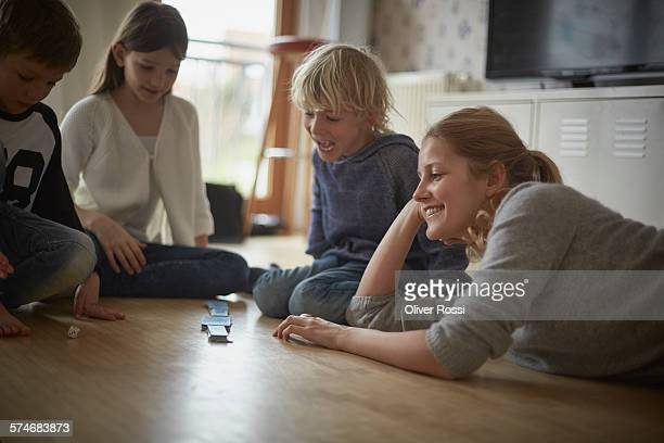 Mother with three children playing on floor