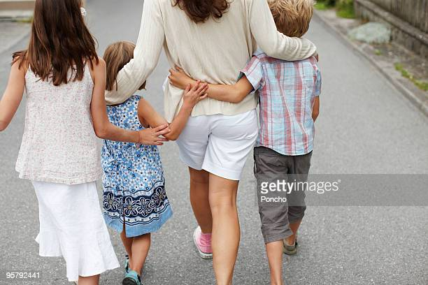 mother with three children walking and hugging