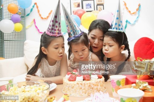 Mother with three girls celebrating a birthday, blowing candles on cake : Stock Photo