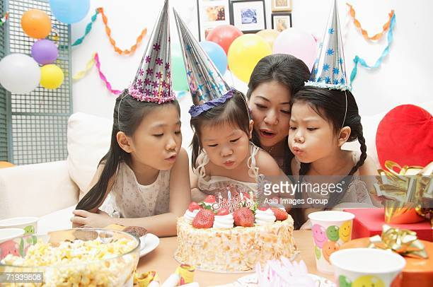 Mother with three girls celebrating a birthday, blowing candles on cake