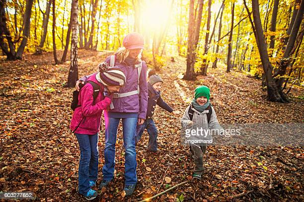 Mother with three kids having fun in autumn forest