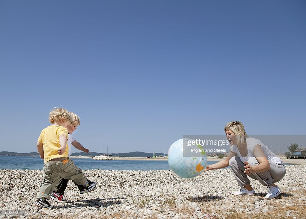 Mother with twins at beach playing ball : Stock Photo